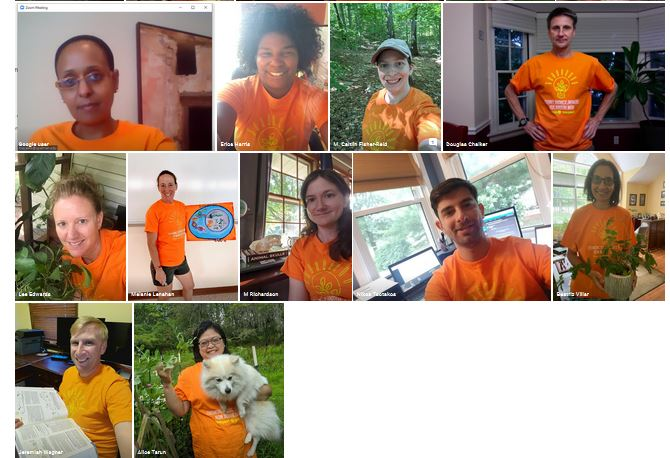 people in orange biome shirts holding something representing their research interests